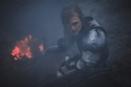 Girl in armor and with sword in her hands kneels against background of fire and black smoke. Closeup.