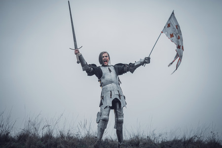 Girl in image of warrior stands in armor and issues battle cry with sword raised up and flag in her hands against background of sky and dry grass. Archivio Fotografico