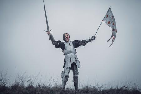 Mädchen im Bild des Kriegers steht in der Rüstung und gibt Kampfschrei mit der angehobenen Klinge und Flagge in ihren Händen gegen Hintergrund des Himmels und des trockenen Grases aus. Standard-Bild