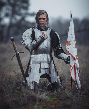 鎧を身につけた少女は、乾いた草を背景に牧草地に旗を持ち、剣を持ってひざまずく。