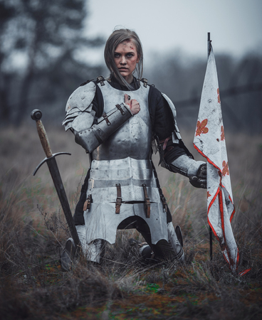 Girl   in armor kneels with flag in her hands and sword on meadow against background of dry grass. Фото со стока