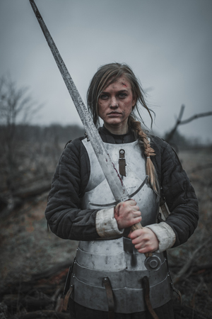 Girl   with wounds on her face stands on meadow in armor and with sword in her hands. Archivio Fotografico