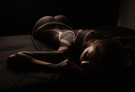 Beautiful young girl with painted body lies on bed. Body art.