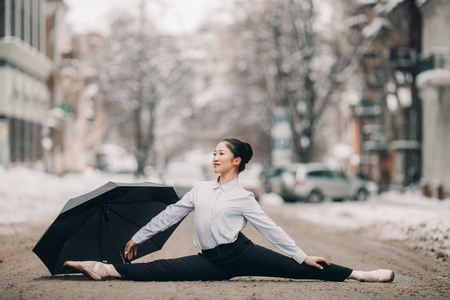 Ballerina with umbrella is sitting in gymnastic pose twine in middle of city street against snow and buildings background. Stock Photo