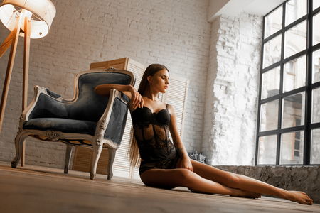 Beautiful young woman in black lace body suit sits on wooden floor next to armchair and lamp against background of brick wall and window. Bottom view.