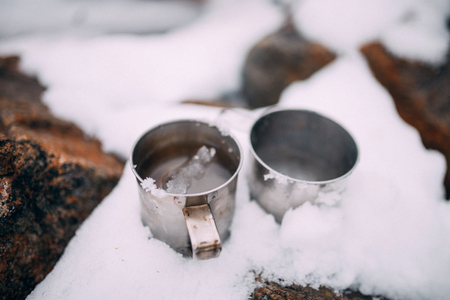 Two metal mugs with melted snow inside stand in snow among rocks. Closeup.