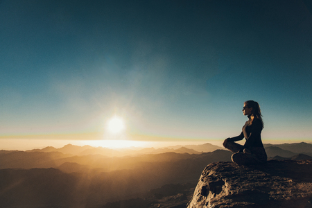 Woman sits in a pose of yoga on edge of cliff on Mount Sinai and meditates against background of beautiful sunrise in Egypt.