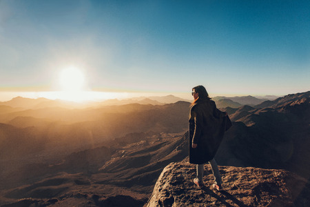 Woman stands on edge of cliff on Mount Sinai and looks at beautiful sunrise in Egypt.