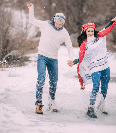 Young couple has fun in park and rides on frozen puddle covered with melted water. Water splashes fly apart and youth laughs cheerfully. Stock Photo
