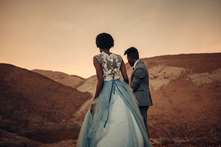 Black happy newlyweds walk in canyon against beautiful landscape at sunset. Back view. Reklamní fotografie