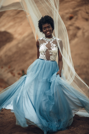 Black smiling bride in long wedding dress and bridal veil stands on background of beautiful landscape.