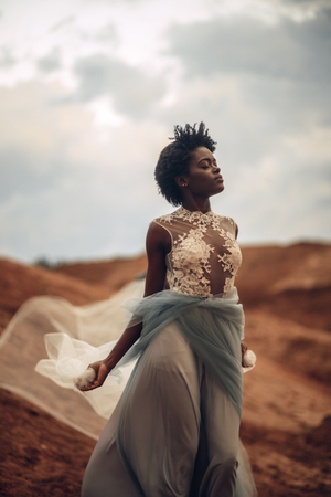 Black happy bride in waving long wedding dress and bridal veil stands on background of beautiful landscape and sky with clouds.