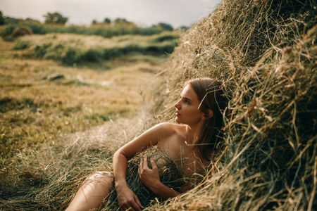 Young naked woman lies near haystack on meadow. Standard-Bild