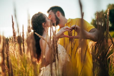 Young enamored couple kisses and makes shape of heart by their fingers at meadow against background of grass and spikes.