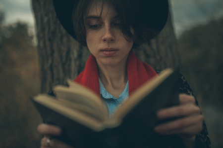 Young woman with book in her hands sits next to tree trunk and reads during of dusk.