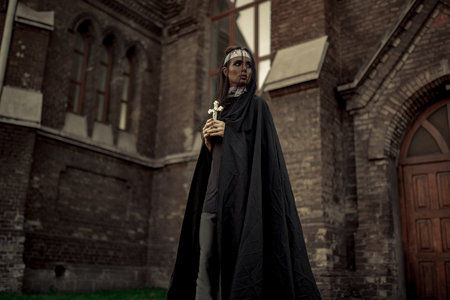 Beautiful young nun in black cassock, cloak and transparent cape is standing with cross in her hands on temple background.