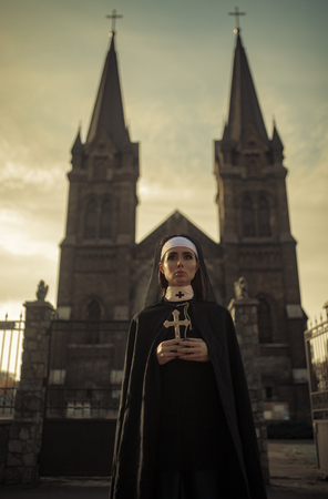 Beautiful young nun in black cassock and cloak is standing with cross in her hands on temple background.