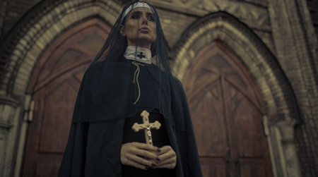 Beautiful young nun in black cassock, cloak and transparent cape is standing and praying with cross in her hands on temple background. Closeup. Zdjęcie Seryjne