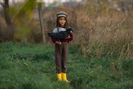Child girl in cap stands with black raven in her hands on background of green grass and trees.