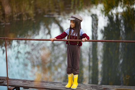 Child girl in cap and yellow rubber boots stands on wooden bridge on background of river.