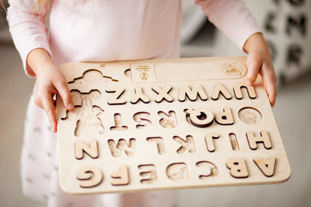 A girl stands and holds in her hands a childrens wooden alphabet. Top view. Closeup. Stock Photo