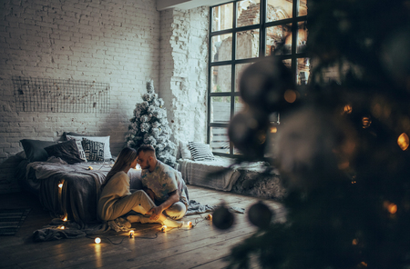 Young couple in love sitting on floor near bed and hugging on background of Christmas tree, glowing lightbulbs, brick wall and window.