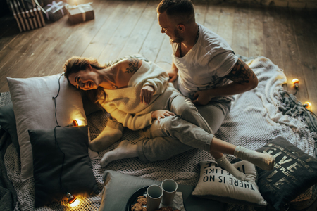 Young couple in love having fun and laughing cheerfully on background of wooden floor, coverlet, pillows and glowing lightbulbs.
