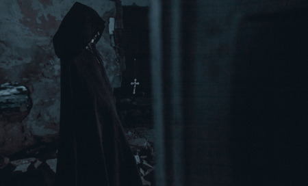 Woman dressed in a black hooded cloak is standing in a darkness next to the cross flying in the air in an image of a nun possessed by demons. Cosplay.