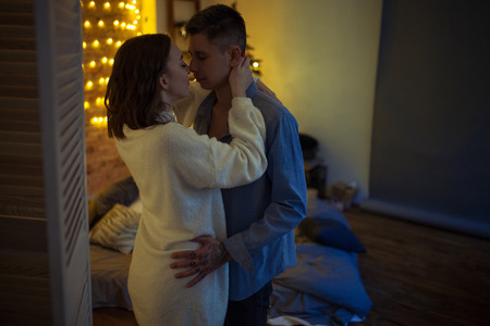 Young lovers are in a hug during on background of the bed and lights in dark room.