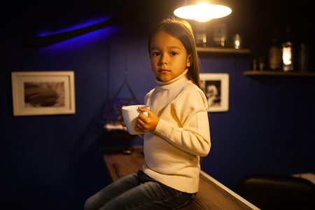 Child girl in a white sweater sits illuminated by light bulb with a cup of tea in her hands.