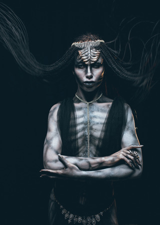 A young woman in the image of a humanoid and extraterrestrial alien with horns on her head and a pattern on the body like a reptile.