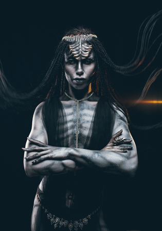 Young woman in image of humanoid and extraterrestrial alien with horns on her head and pattern on body like reptile on background of light.