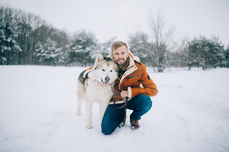 Young man sits in the snow next to a dog Alaskan Malamute and hugs his for a walk in winter. Banque d'images
