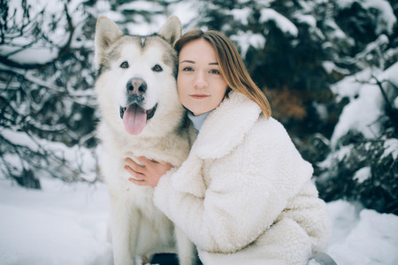 Girls is hugging dog Alaskan Malamute for a walk in winter forest against pines background.