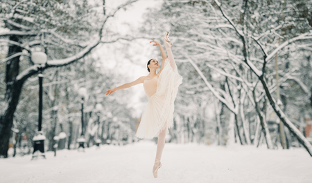 Beautiful ballerina in transparent skirt is dancing at walkway of snowy city.