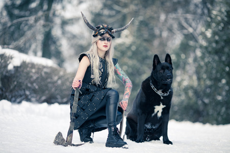Beautiful warrior woman in image of viking with horned helmet on her head and ax in her hand next to the big black dog in winter forest.