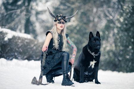 Bella donna guerriera a immagine di vichingo con elmo cornuto sulla testa e ascia in mano accanto al grosso cane nero nella foresta invernale.