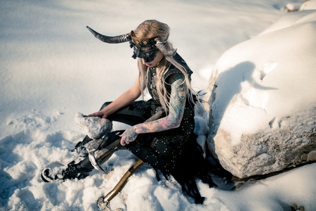 Beautiful warrior woman in image of viking with horned helmet on her head and ax in her hand sits on snow next to big stone. Stock Photo
