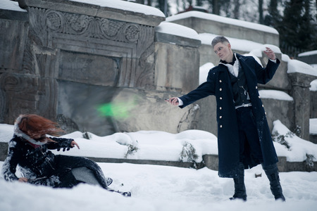 Battle of dark and light magicians with the help of magic wands and green beam on the snow background.