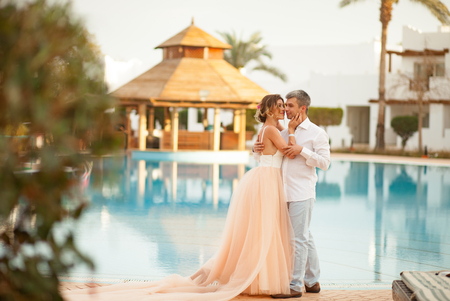 Happy newlyweds stand and hug on the villa next to the swimmimg pool during the honeymoon in Egypt.