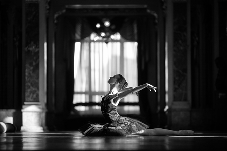Beautiful ballerina dancing in a hall against the window. Black and white image.