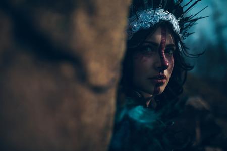 Portret van een jonge vrouw in het beeld van een fee en een tovenares die naast de rots staan in een zwarte jurk en een kroon.