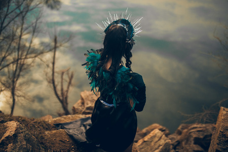 A young woman in the image of a fairy and a sorceress standing next to rocks over a lake with the reflection of the clouds in a black dress and a crown. Back view.