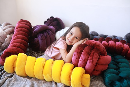 Child girl lies on the bed among unusual multicolor pillows in pajamas.