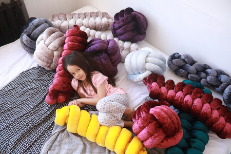 Child girl lies on the bed among unusual multicolor pillows in pajamas. Top view. Banque d'images