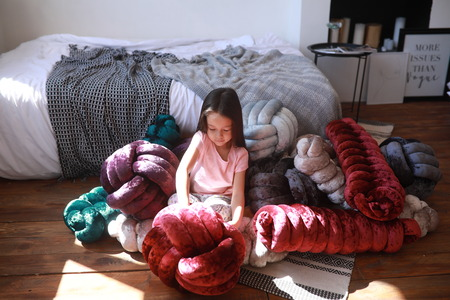 Child girl plays on the floor among unusual multicolor pillows in pajamas against background of the bed. Stock fotó