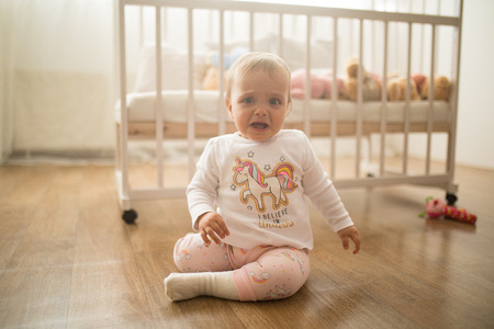 A sad toddler sits on the floor and cries against background of the crib.