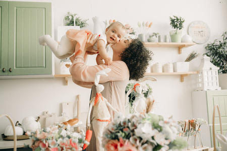 Happy mother plays and kisses her baby in the kitchen on background of easter decorations. Archivio Fotografico