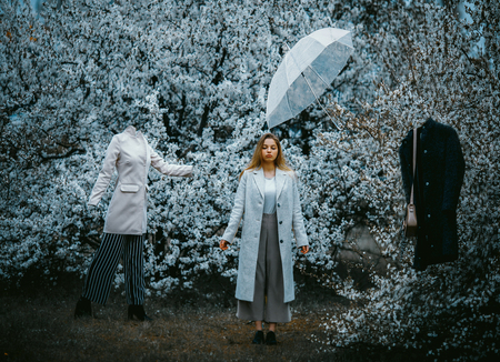 A young woman stands in a blooming garden among mannequins and an umbrella flying in the air. The concept of levitation. Stock fotó - 122402730