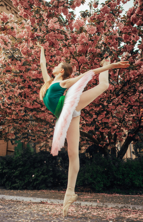 Ballerina standing in arabesque pose in a beautiful tutu against the background of flowering sakura trees in the park alley. Imagens